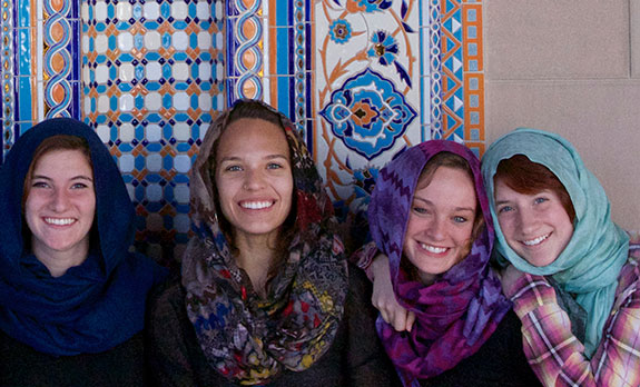 Liberty University students pose in front of a tapestry in a Middle Eastern country..