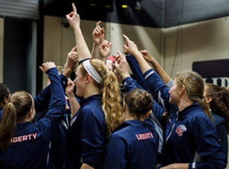 Liberty women's basketball team huddles after a recent victory at Longwood.