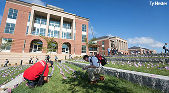 Students plant miniature American flags outside the Jerry Falwell Library on Friday.