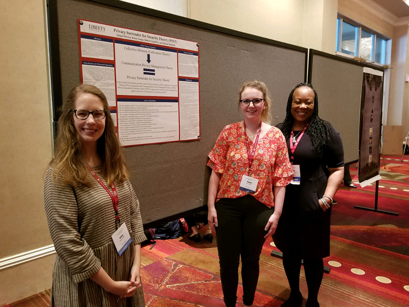 Kasey, Dr. MG, and Abby standing with our poster presentation at ECA!