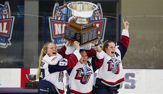 Liberty captains Courtney Gilmour (left), C.J. Tipping, and Vanessa DeMerchant raise the ACHA Division I women's hockey championship cup. (Photo by Joel Coleman) test test test test
