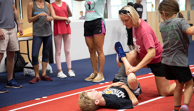 Club Sports Assistant Athletic Director for Sports Medicine Angie Witt helps participants stretch after Wednesday's Ninja Warrior Challenge Kids Camp, held in conjunction with Saturday's State Games of America event at the Liberty Indoor Track Complex. test test test test