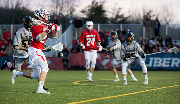 Liberty junior midfielder Chase Wright sends an entry pass from the top of Colorado's box in front of sophomore teammate Carter Elliott (24) in Friday's 17-15 setback. (Photo by Nathan Spencer) test test test test