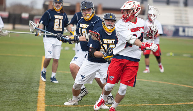 Flames senior midfielder Brett Bernardo is surrounded by West Virginia players as he looks for a teammate to pass to, Saturday at the Liberty Lacrosse Field. test test test test