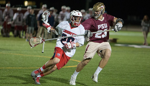 Liberty junior midfielder Bryce Mrakovich works past Florida State long-stick defender Ricky Reyes on Friday night. test test test test