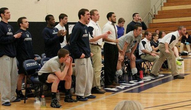 Messiah College wrestler Chris Williamson (center) encourages his teammates from the sideline during a match last season. test test test test