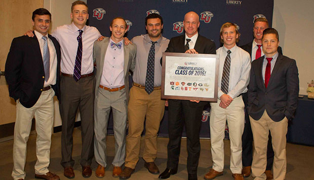 Members and coaches of the Flames' men's lacrosse team present Liberty Senior Vice President for Auxiliary Services Lee Beaumont with a plaque expressing their appreciation for his support of the Club Sports program. test test test test