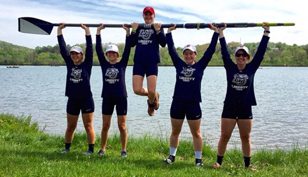 Liberty's Women's Novice 4 rowers Kendra Dowdy and Gabby Kitchens (left) and Allie Coughlan and Sarah Catto (right) hoist coxswain Lydia Miller as she does a pull-up on their oar. 