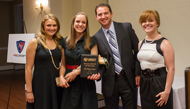 Liberty director of Club Sports Kirk Handy and special projects coordinator Karen Kittinger (right) present senior gymnast Jill Wippermann with the Female Athlete of the Year award as she is accompanied by coach Rachel Steele (left). test test test test