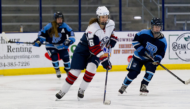 Sophomore forward Danica Polson skates the puck between two Rhode Island players Saturday. (Photos by Gabrielle Calhoun) test test test test