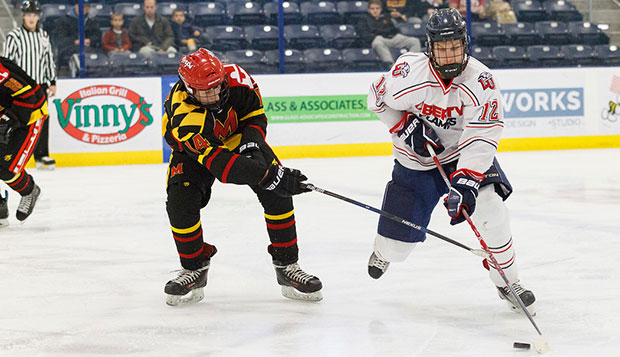 Liberty senior forward Devon Docksteader controls the puck beside a Maryland player Saturday at the LaHaye Ice Center. test test test test