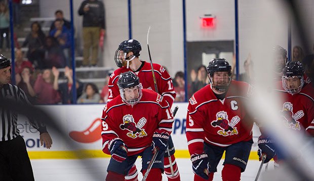 Liberty senior defenseman and head captain Ben Hughes (5) celebrates a Flames goal with forward teammates (from left) Grant Garvin (17), Quinn Ryan (19), and Zechariah Roberts (right) in a recent game at the LaHaye Ice Center. test test test test