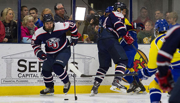 Liberty junior forwards Kyle Garcia (18) and Danny Logan work along the boards in last Friday's loss to Delaware at the LaHaye Ice Center.  test test test test