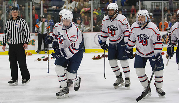 Liberty players celebrate a goal by sophomore forward DJ Dinnison (left) that set off the Teddy Bear Toss in a 3-2 overtime win over West Virginia, Feb. 15 at the LaHaye Ice Center. test test test test