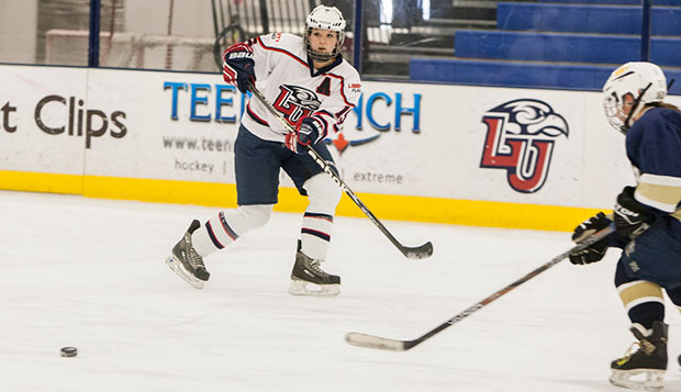 Liberty senior defenseman Autumn Kucharczyk eyes the puck beside a Navy player during the Lady Flames' 17-0, 16-0 weekend sweep at the LaHaye Ice Center. test test test test