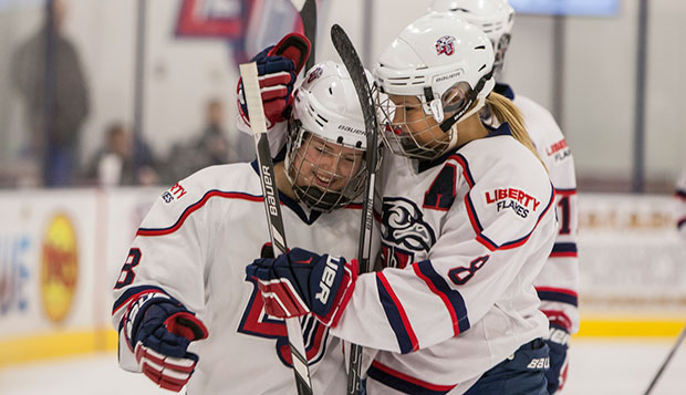 Liberty senior Jenny MacArthur (right) congratulates freshman Chelsey Greenwood on her first goal as a Lady Flame, Saturday at the LaHaye Ice Center. test test test test