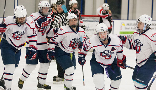 Liberty's top line, including forwards Carrie Jickling (C), Courtney Gilmour (92), and Catharine Burrell (14) celebrate a goal in a recent game at the LaHaye Ice Center. test test test test