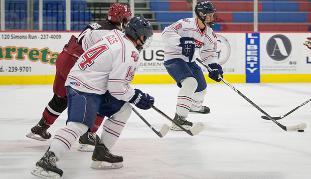Liberty freshman forward Devon Docksteader (18) handles the puck in front of sophomore forward Paul Ingles on transition at the LaHaye Ice Center. test test test test