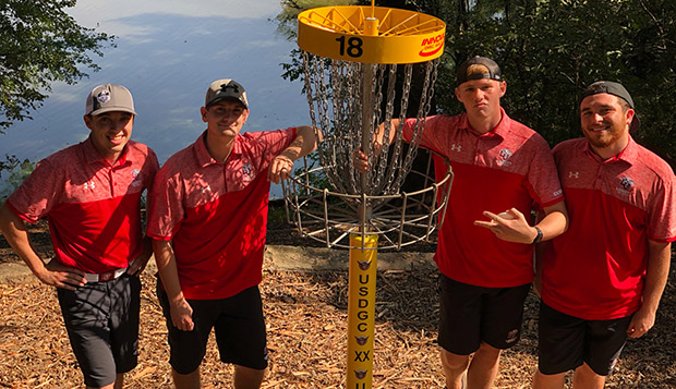 The Flames' championship team of Jeremy Miekley (left), Hunter Thomas, Pete Curran, and Ryan Shumate pose beside the 18th hole at the Winthrop Gold course Saturday in Rock Hill, S.C. test test test test
