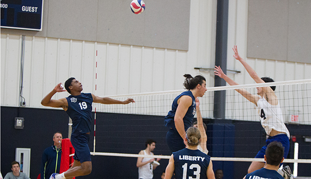 Flames junior outside hitter Gene Dejesus spikes off a set from sophomore Kaden Knepper in an ECVA South Play Date match played Feb. 11 at Liberty. (Photo by Jessie Rogers)