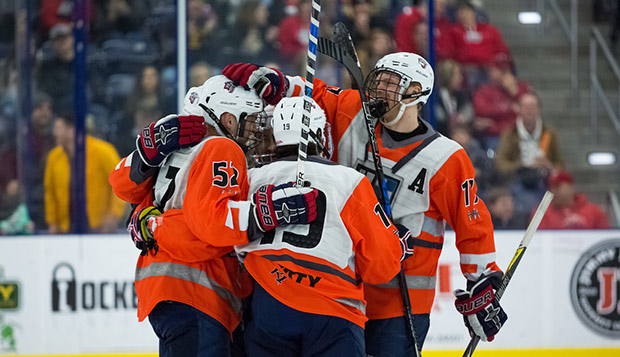 The Flames, dressed as rebel fighter pilots, celebrate a goal by junior defenseman Zane Schartz (52) in a five-goal first period. (Photos by Nathan Spencer) test test test test