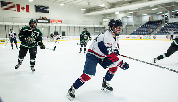 Liberty sophomore forward Jamie Crane skates along the boards against the Bobcats on Friday at the LaHaye Ice Center. (Photo by Joel Isimeme)