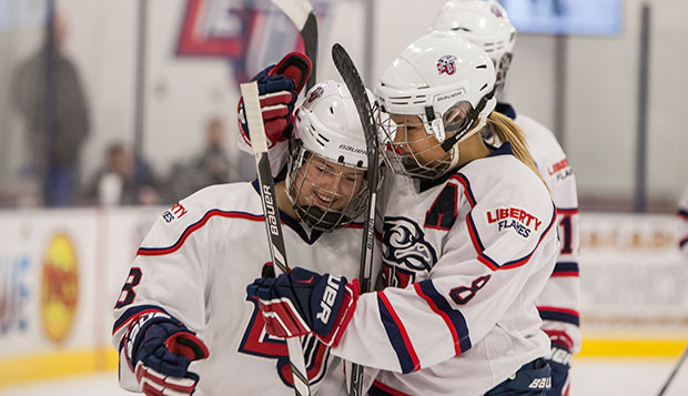 Former Liberty forward Jenny MacArthur (right) shows her mentoring side as she congratulates then-freshman forward Chelsey Greenwood following her first goal as a Lady Flame on Feb. 7, 2015, in a game against Navy at the LaHaye Ice Center.   test test test test