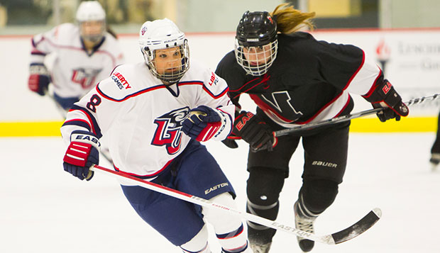 Liberty junior forward Jenny MacArthur tries to beat a Northeastern player to the puck. She had a goal and two assists in the No. 7 Lady Flames' 10-1 triumph over the No. 10 Huskies, Sunday morning at the LaHaye Ice Center. test test test test