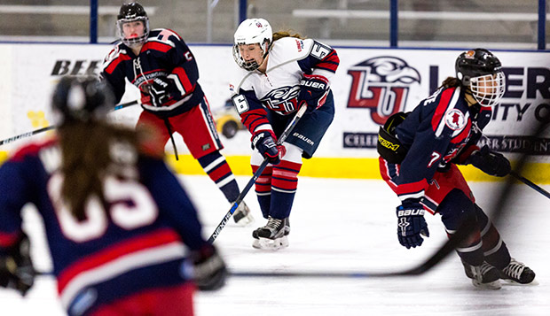 Liberty junior defenseman Katie Comeau skates between opposing players in a March 3 game. (Photo by Joel Isimeme)