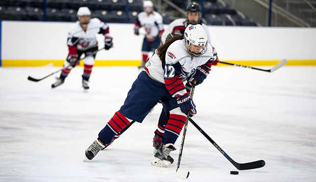 Liberty forward Kira Rice skates the puck up the ice in a recent home game. (Photo by Jessie Rogers) test test test test
