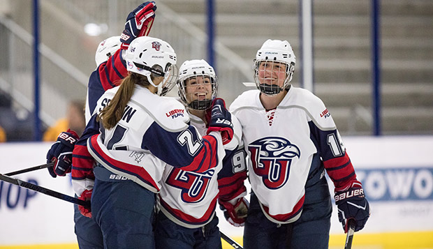 Liberty defenseman Kristi Serafin (left) and forwards Tiana Lisle and Shannon Fehr celebrate a goal in Friday night's opener against Grand Valley State at the LaHaye Ice Center. (Photo by Joel Isimeme) test test test test