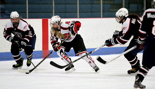 Lady Flames forwards Courtney Gilmour (left) and Nikki McCombe close in on a Davenport player during their 5-0 victory over the Panthers on Friday at the Patterson Ice Arena. test test test test