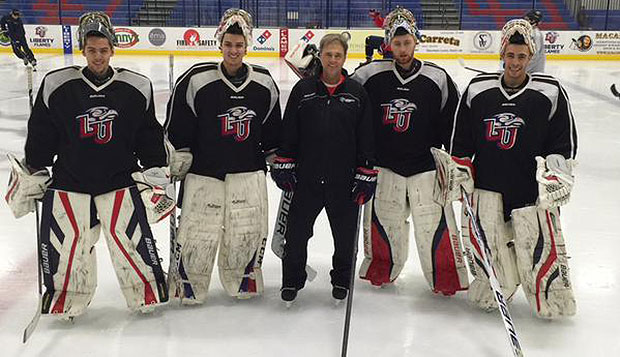 New goalies coach Daniel Berthiaume poses with (from left) freshman Josh Halpenny, senior Cary Byron, sophomore Matt Pinel, and senior Ian Harris, at the Flames' practice this week. test test test test