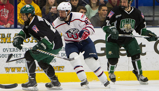 Liberty senior forward Ryan Kerr battles along the boards between two Bobcats during Friday night's opener against Ohio at the LaHaye Ice Center. test test test test