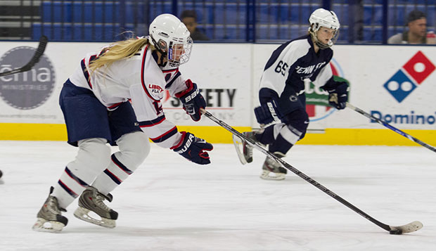 Liberty junior forward Catherine Burrell controls the puck beside a Penn State player in the Lady Flames' 6-5 victory, Dec. 5 at the LaHaye Ice Center. test test test test