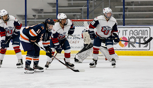 Lady Flames senior defenseman Emily John (4) and sophomore forward Grace Machholz (right) guard the cage in a home game last weekend against Midland. (Photo by Jenna McKenney) test test test test