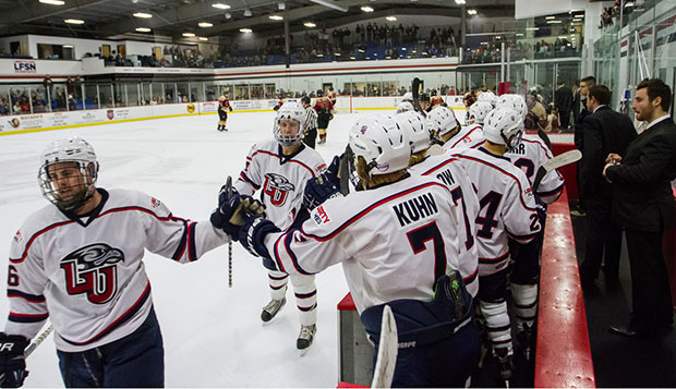 Liberty junior forward Lindsay LeBlanc (left) leads a line in celebration of a goal with Flames' teammates on the bench during last Friday's 4-2 victory over Rochester (Mich.) College. test test test test