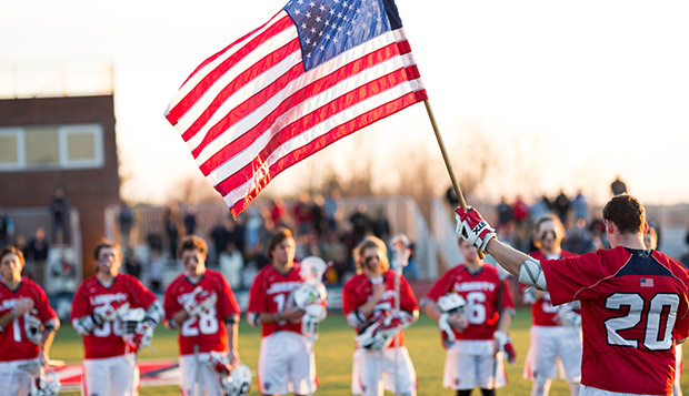 Junior midfielder Chase Wright waves the flag before a March 9 game at the Liberty Lacrosse Fields. (Photo by Nathan Spencer) test test test test