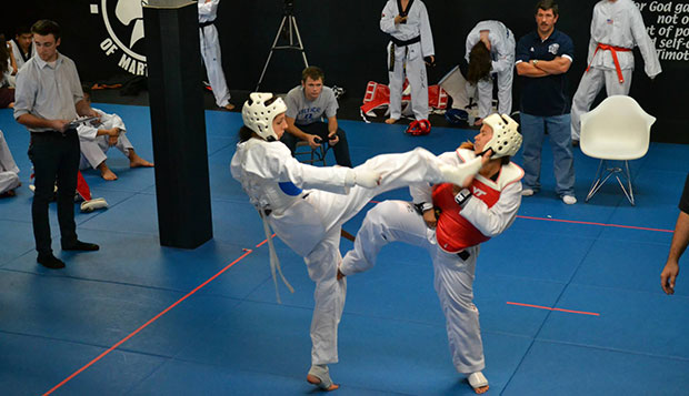 As head coach Jesse Wilson (right) looks on, Liberty freshman Michelle Rowell lands a kick to the head of Virginia Tech's Kat O'Malley during a competition Sept. 15 at the Renaissance Academy of Martial Arts in downtown Lynchburg. test test test test