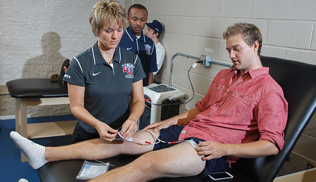 Liberty Club Sports head athletic trainer Angie Witt (left) uses electronic stimulation therapy on hockey player Ryan Kerr's deep thigh bruise as assistant Cordell Hood looks on, Thursday morning in the new Club Sports athletic training room. test test test test