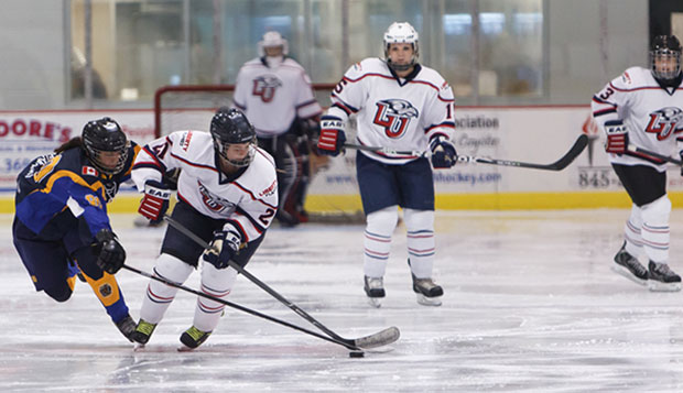 Liberty freshman Courtney Gilmour (21), who played for the Hamilton Hawks last season, battles for a loose puck beside Autumn Kucharczyk (15) and fellow freshman Marissa Graham (right), who scored the Lady Flames' first goal. test test test test