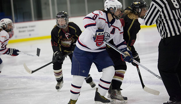 Lady Flames forward Nikki McCombe (9) battles with an Eagles player during their extremely competitive series over the weekend at the LaHaye Ice center. test test test test