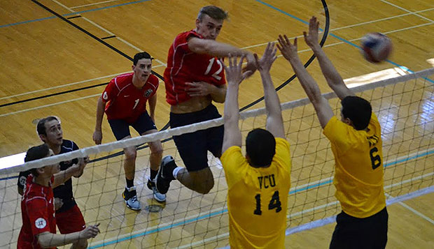 Liberty sophomore middle hitter Luke Werth spikes through a block in a match against Virginia Commonwealth University. test test test test