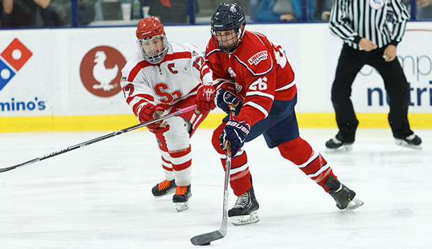 Liberty sophomore forward Marshal King works the puck past a Stony Brook defenseman during a recent series against the Seawolves at the LaHaye Ice Center. test test test test