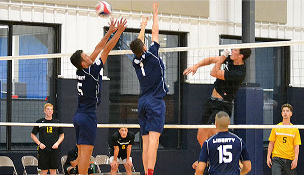 Liberty sophomore outside hitter Nick Williamson (5) and junior middle blocker Si Hershberger (1) put up a block in a home match last month as freshman TJ Forsythe (15) looks on. test test test test