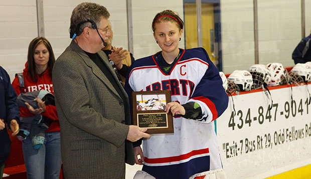 Patti Smith receives an award from Lady Flames Head Coach Paul Bloomfield on Senior Night at the LaHaye Ice Center for being a four-year Academic All-American. test test test test