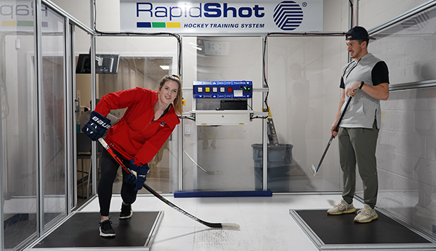 Lady Flames DI women's hockey forward Vanessa DeMerchant and DI men's forward Quinn Ryan train side-by-side in the new RapidShot booth. (Photos by Ted Allen)  test test test test