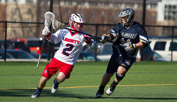 Liberty freshman attack Sam Gregory fends off George Washington defender Lars Chinburg during the Flames' 16-2 victory Saturday at home. test test test test