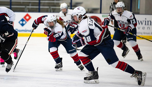 Junior forward Shelby Burden (9) and sophomore defenseman Sarah LaPorte (13) pursue the puck in a Sept. 8 game at the LaHaye Ice Center. (Photo by Jessie Rogers) test test test test