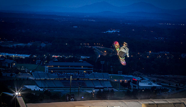 With the Peaks of Otter and Williams Stadium providing a scenic backdrop, a snowboarder executes an aerial stunt off a jump late one night at the Liberty Mountain Snowflex Centre. test test test test